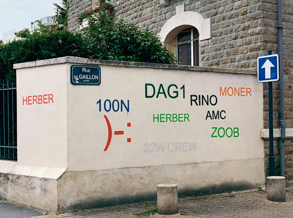 Artist paints over 'tag' graffiti with legible typefaces.