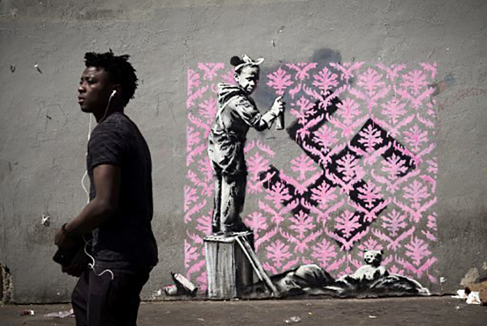 Black girl sprays a pink wallpaper pattern over a swastika.
