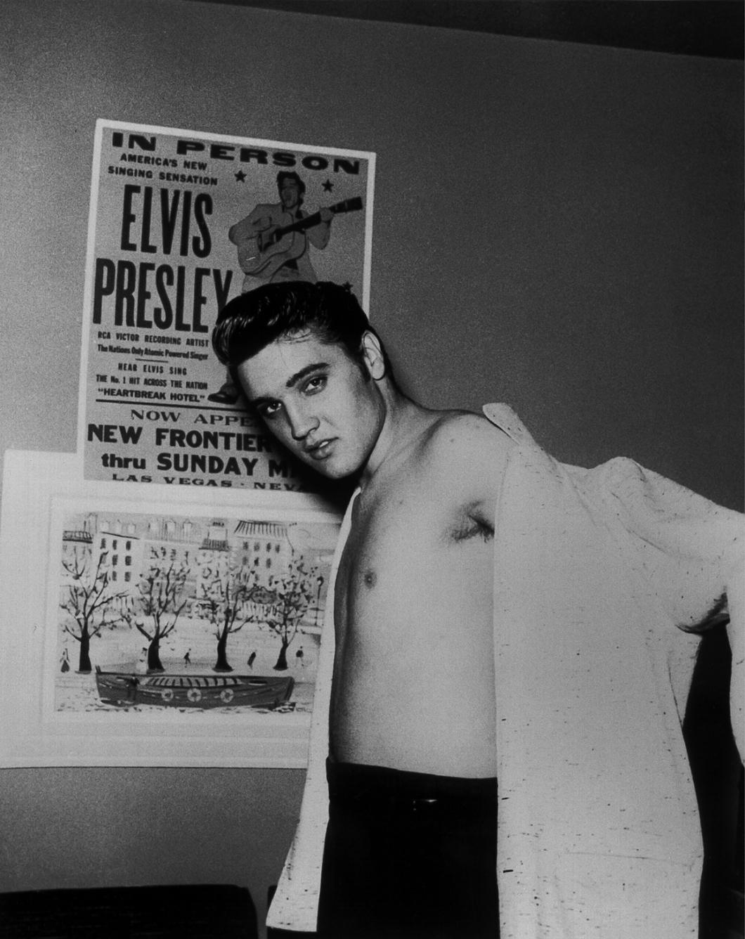 Elvis posing in front of one of his posters
