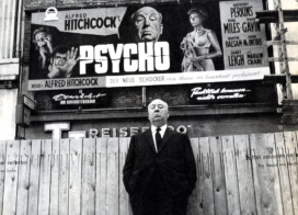 Hitchcock poses in front of a billboard for Psycho, 1960