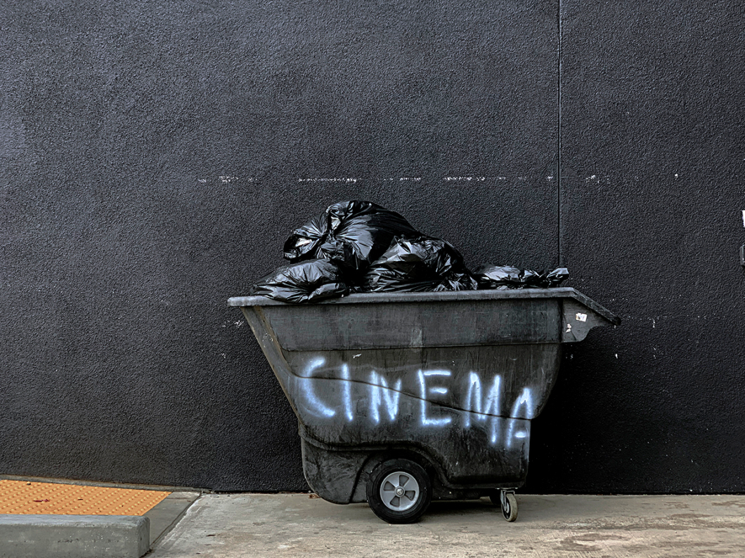 Photo of a tip full of rubbish with the word cinema sprayed on its side.